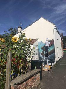 Artist DMK working on the Viking mural on Bere Lane scaled