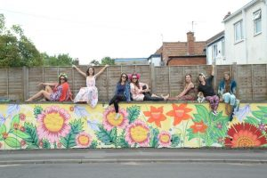 Artists Kim Sophie with friends at the newly painted Flower mural on Manor House Road