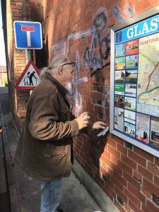 Bruce Denney helping clean some unwanted and messy tagging in Glastonbury town centre. scaled