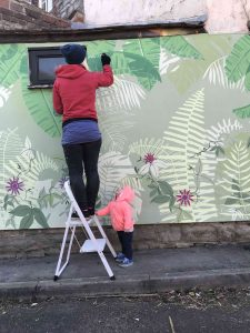 Faye Suzannah painting the Passionflower jungle mural watched by her daughter scaled