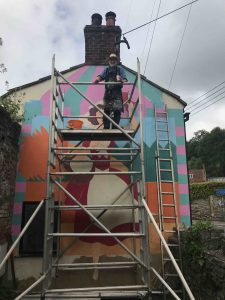 Frank Harwood posing for a quick photo op whilst working on his waving woman mural on chilkwell street scaled