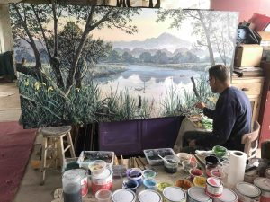 Jon Minshull working on his Avalon Marshes Mural painted on board using paints by local eco company Thorndown Paints scaled