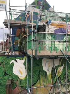 Julia Bedford at work on the Swan with Lillies Mural at number 1 barbers on Northload street scaled