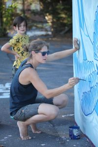 Kim works on her painting of a swallow at the mural trail launch at glastonbury skatepark