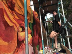 Oksana working on scaffolding provided by R4 whilst painting her mural on the Globe Inn scaled