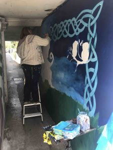 Rachel Blackwell working on her dragon mural in the tunnel scaled