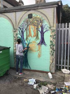 Tonia painting Trees as part of the Wildwood Mural on Silver Street scaled