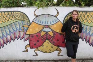 kim infront of the winge dbug mural