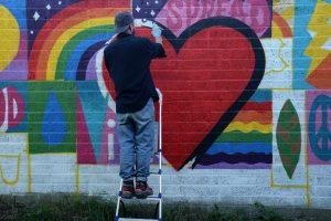 Luke Embden painting the Spread Love mural